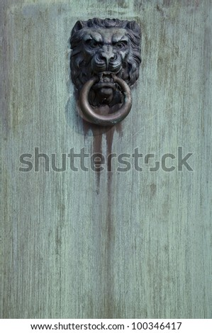 An aged and weathered lion head door knocker on a weathered painted wood door. - stock photo