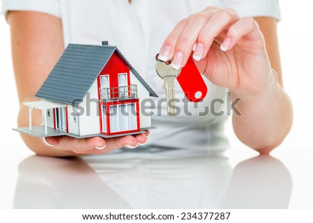 an agent for property with a house and a key. successful leasing and property for sale by real estate agents. - stock photo
