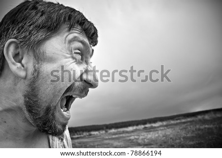 an aggressive angry man screaming - stock photo