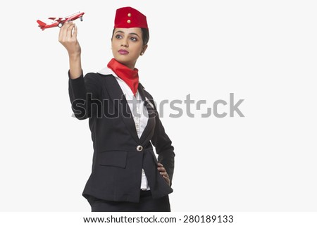 An airhostess looking at toy airplane isolated over white background - stock photo