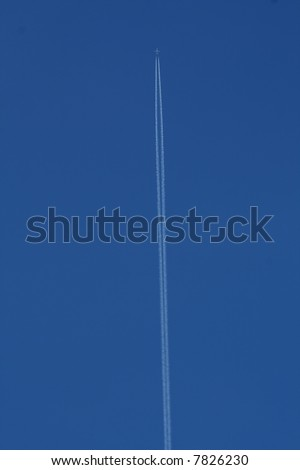 An airliner leaves a vapour trail across a cloudless blue sky - stock photo