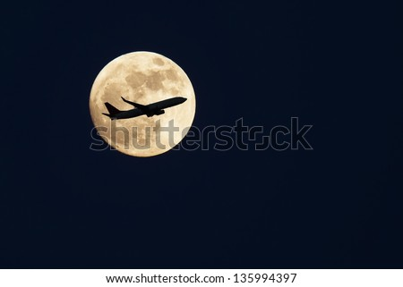 an airplane flying across a full moon - stock photo