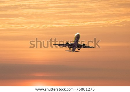 An airplane flying in the orange sky - stock photo