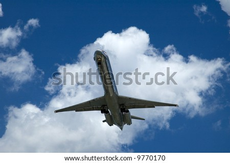 An airplane is landing with a blue sky against a white puffy cloud - stock photo