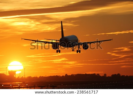 An airplane landing at an airport during sunset on vacation during a journey - stock photo