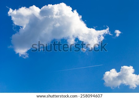 An airplane passes high in the sky between two white clouds against a blue sky background. - stock photo