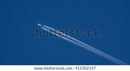 An airplane trail across the blue sky - stock photo
