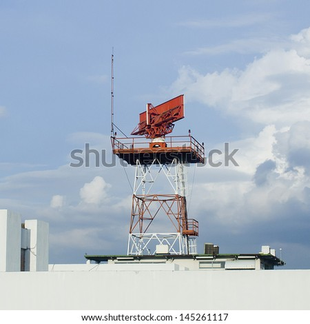 An airport surveillance radars on a bright blue sky background, situated on a terminal area. - stock photo