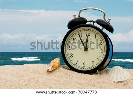 An alarm clock with seashells sitting on the sand with water, vacation time - stock photo