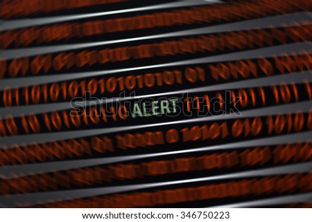 An alert text is on the screen. The word is in green and ones and zeros are in red. There is a blur effect applied to the image to emphasize the alert word. - stock photo