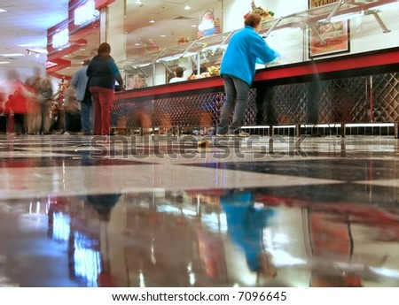 an all you can eat pizza/cafeteria joint - the shot is from the checkered floor looking across at the food line and with a time exposure, some of the customer movement is blurred - stock photo
