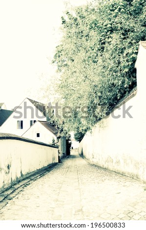 An alley behind a house that has a long wall on the right side of it. - stock photo