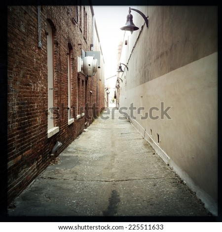 An alley with a two toned wall with street lamps and a brick wall with windows. - stock photo