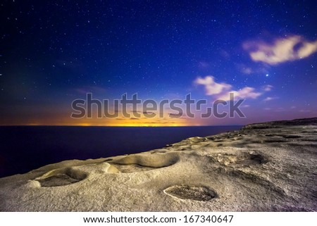 An almost alien and surreal landscape...actually shot on the island of Gozo.  The distant glare and lights are from the island of Sicily. - stock photo