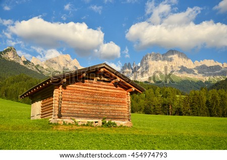 An Alpine meadow with old wooden farmhouse, Dolomites, Italian Alps in summer sunset light - stock photo