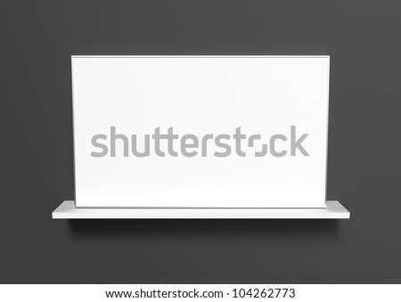 An aluminum frame with a white picture standing on a white shelf on a black background. - stock photo