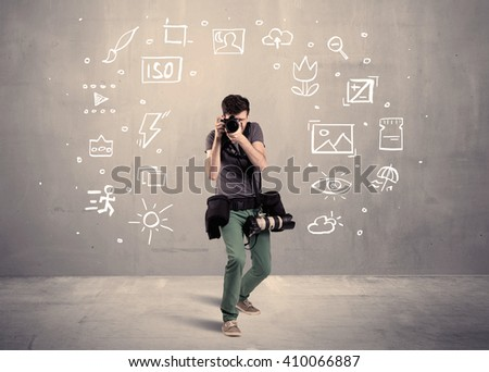 An amateur hobby photographer learning to use a professional digital camera with camera settings icons on the background wall concept - stock photo