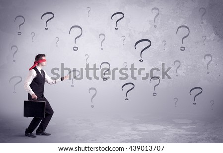 An amateur young sales person lost in a new situation concept with blindfolded businessman surrounded by drawn question marks. - stock photo