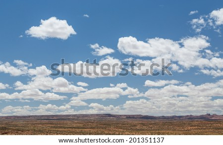 An amazing desert landscape and flying clouds throughout the deep blue sky. - stock photo