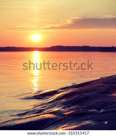 An amazing sunset by the sea. Image taken in Finland during summer evening. Image has a vintage effect applied. - stock photo