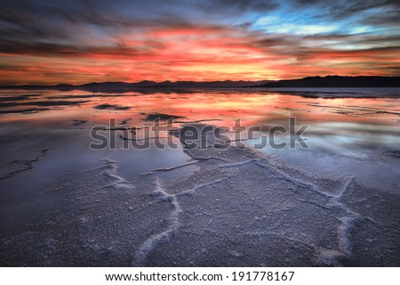 An amazing sunset over the Bonneville Salt Flats. A little residual water from rains provided a nice reflecting pool. - stock photo