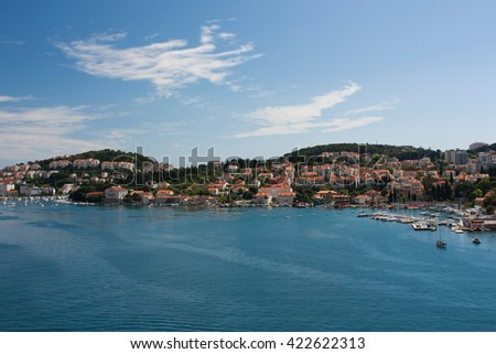 An amazing view from above on Dubrovnik with houses with tegular red roofs and green hills, Croatia. - stock photo