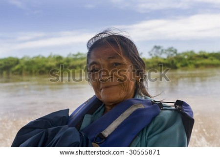 An Amazonian elderly woman riding in a river boat on the Amazon River - stock photo