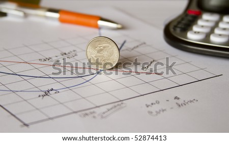 an american coin (quarter) positioned along the negative slope of a graph displaying the economy - stock photo