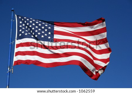 An American flag flaping boldly in the wind. - stock photo