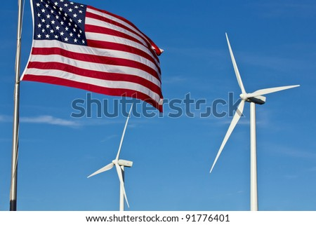 An american flag flies in the foreground, with two wind power generator windmills turn in the background - stock photo