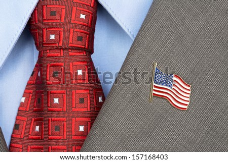 An American flag lapel pin on the collar of a business suit jacket shows patriotism - stock photo