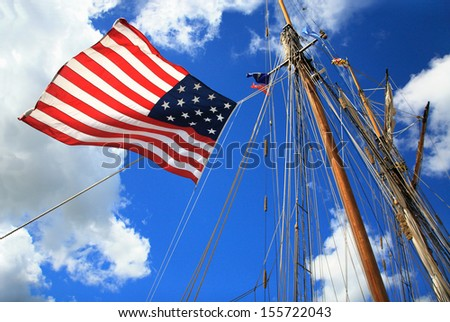 An American Flag, Mast And Rigging Against A Deep Blue Cloudy Sky During The Perry 200 Commemoration, September 2013, Erie Pennsylvania, USA - stock photo