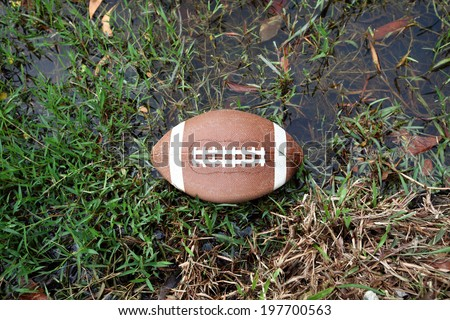 An American football ball on a water logged grass pitch.  - stock photo