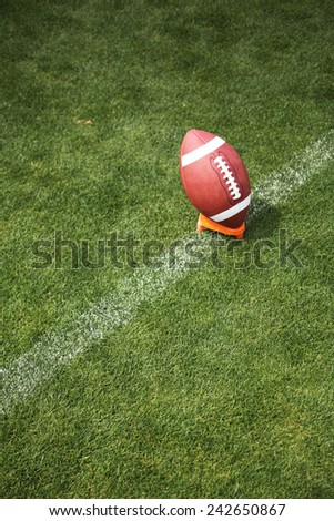 An American football on a green football field  - stock photo