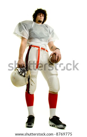 An American football player. Standing with helmet and ball. - stock photo