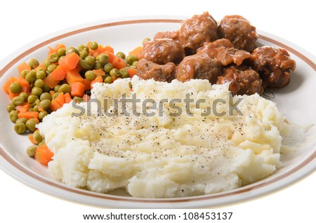 An american supper of mashed potatoes, with sweet and sour meatballs with peas and carrots. - stock photo