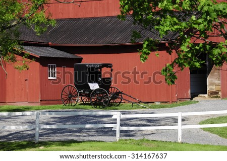 An Amish buggy parked by a red barn in summertime. - stock photo