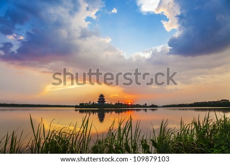 An ancient chinese tower under sunset with colorful clouds in the sky - stock photo