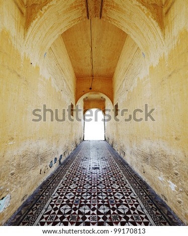 An ancient moorish hallway with exotic pattern tile flooring leading to a doorway. - stock photo
