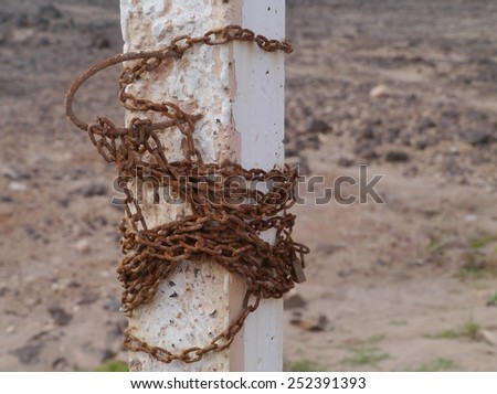 An ancient rusty chain around a white concrete pole in the desert of the Spanish island Fuerteventura one of the Canary islands in the Atlantic Ocean belonging to Spain - stock photo