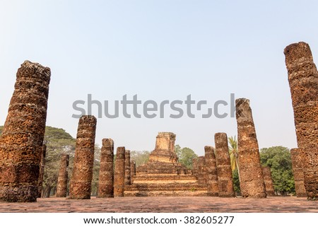 An ancient temple ruin with slanted laterite/sandstone pagoda in the area of Sukhothai's UNESCO world heritage park, Thailand. The place is public property, no release document required. - stock photo