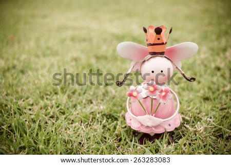 An Angle doll holding three flower on green glass in the temple with vintage style  - stock photo