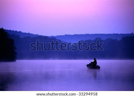 An angler spends a quiet morning on the lake fishing for bass. - stock photo