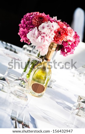an angles image of a pink hydrangea centerpiece and a bottle of champagne on a decorated white table - stock photo