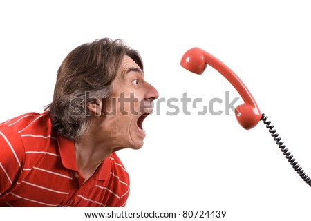 An angry and irritated man screams into the telephone receiver over a white background. - stock photo