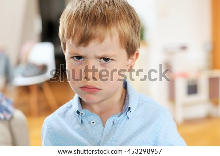 An angry blond and caucasian young boy - stock photo