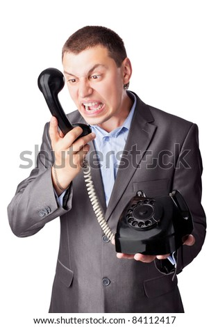 An angry businessman screaming in telephone receiver isolated on white background - stock photo