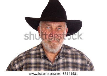 An angry cowboy has a piece of straw in his mouth.  He is wearing a black cowboy hat. - stock photo