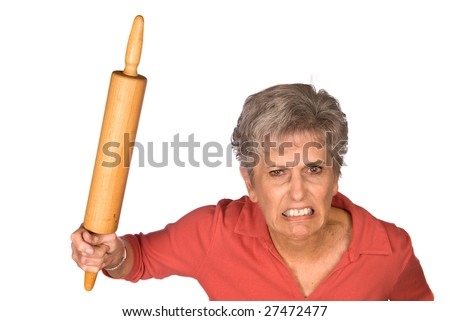 An angry grandmother is ready to swing her rolling pin to fend off unwanted bystranders. - stock photo