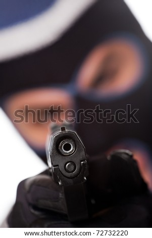 An angry looking man wearing a ski mask pointing a black handgun at the viewer. Shallow depth of field. - stock photo